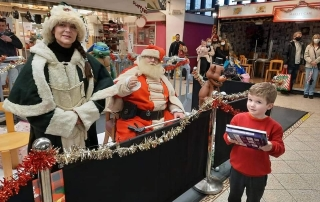 Alan Myatt handing out Christmas presents as Deluxe Father Christmas